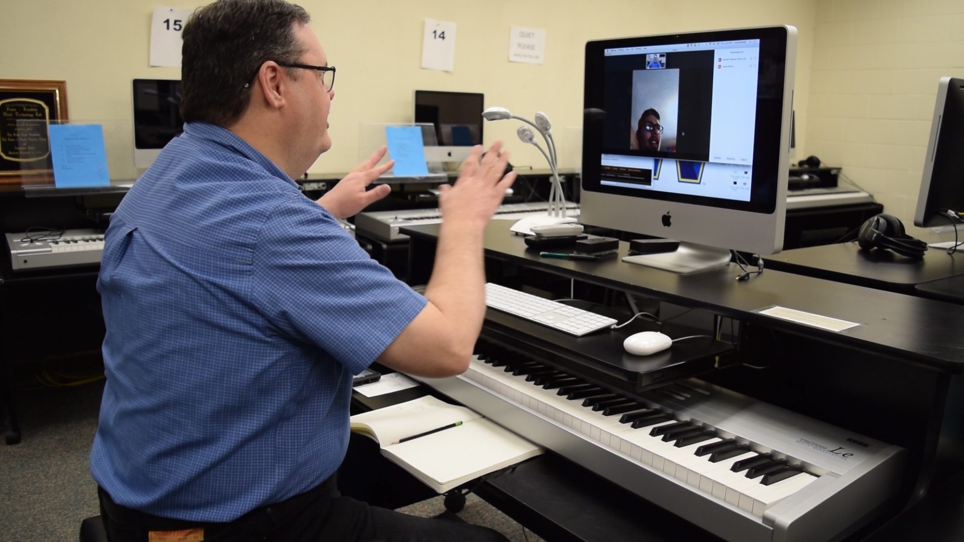 man sitting at electronic piano talking to students through video chat