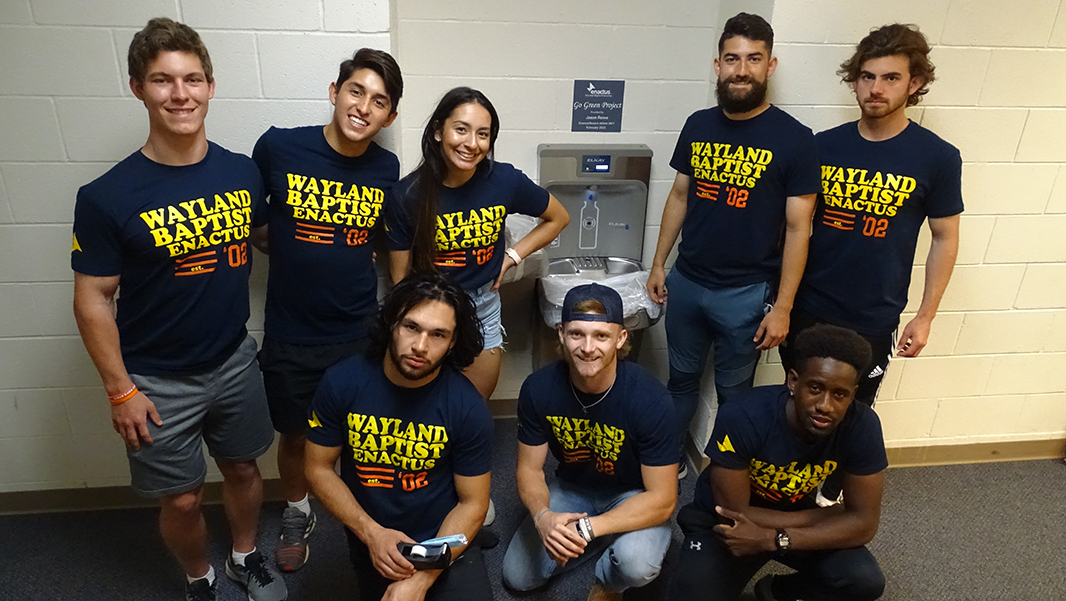 8 students wearing Wayland Enactus t-shirts stand by a water bottel filling station