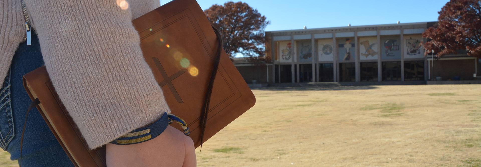 Close up of  student's hand holding a Bible while standing in front of the Harral Memorial Auditorium & Fine Arts Complex.