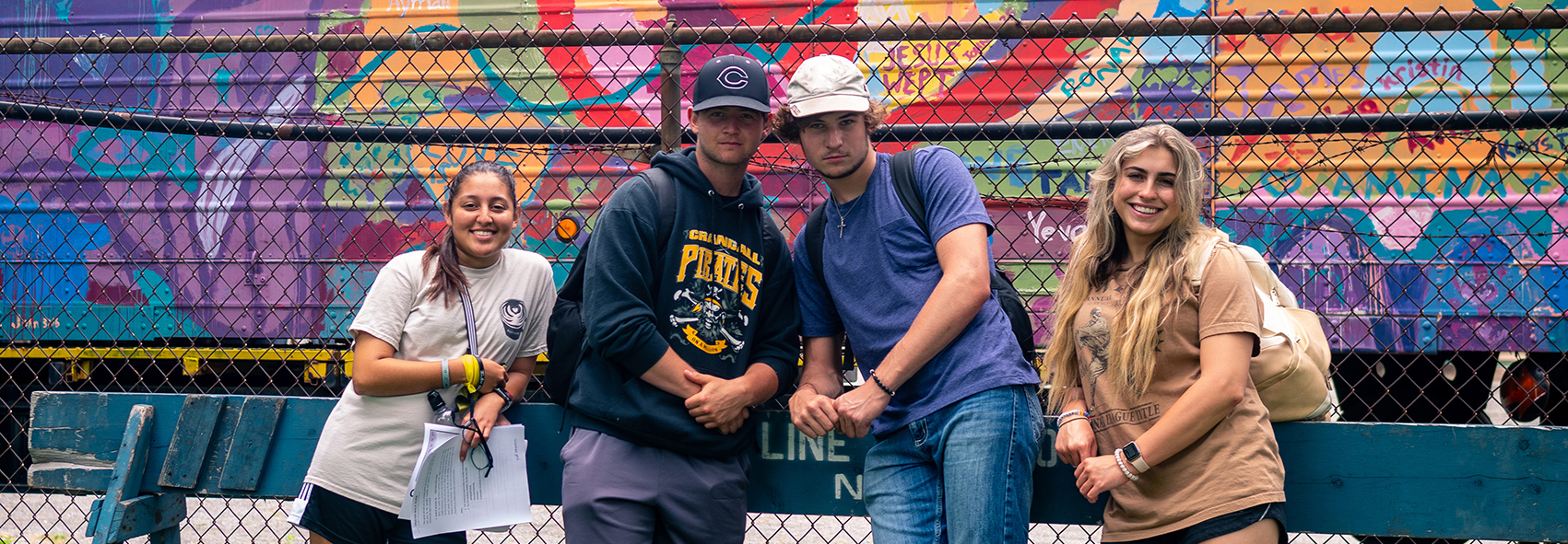 Group of students standing in front of a graffiti wall