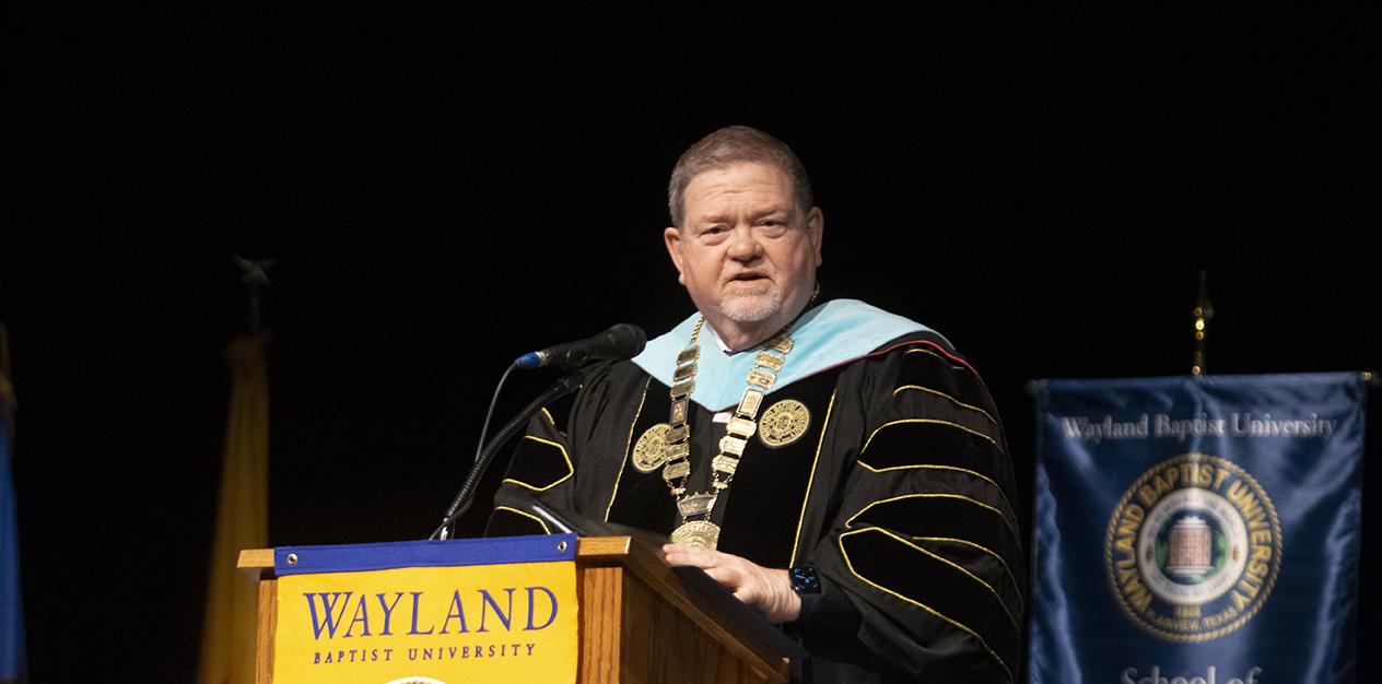 man in full academic regalia standing at a podium speaking