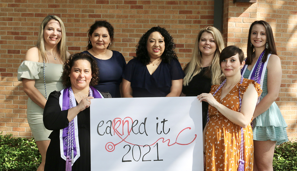 Seven women holding a sign that says 'Earned It.'