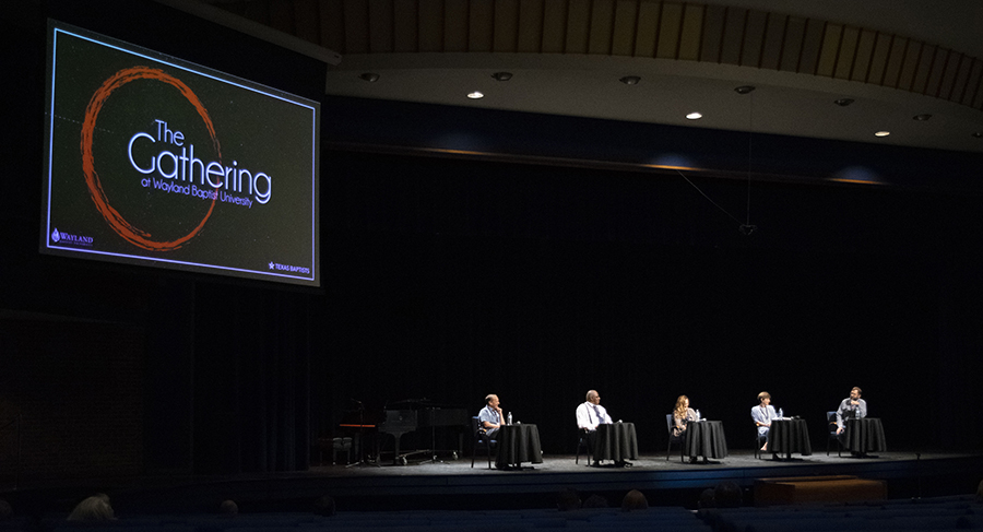 Five individuals sit at small tables on a stage as part of a panel discussion