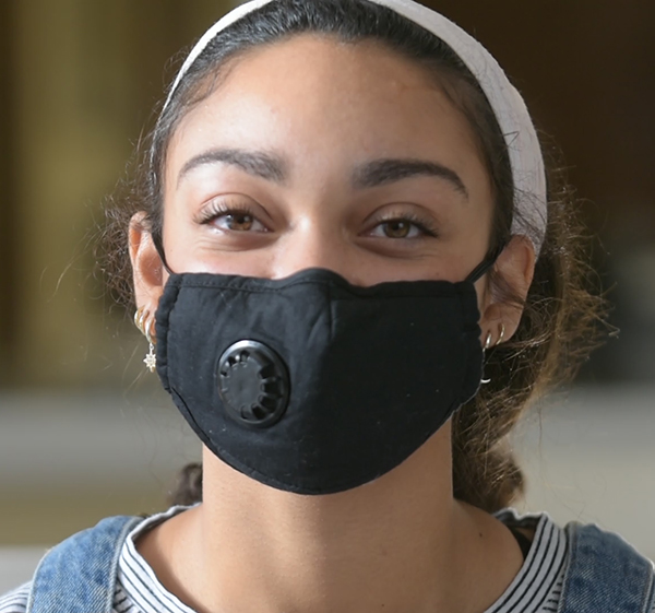 Close up of a young woman with vibrant eyes wearing a black facemask