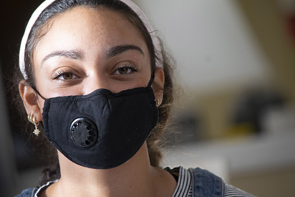 Face of a young woman wearing a black facemask