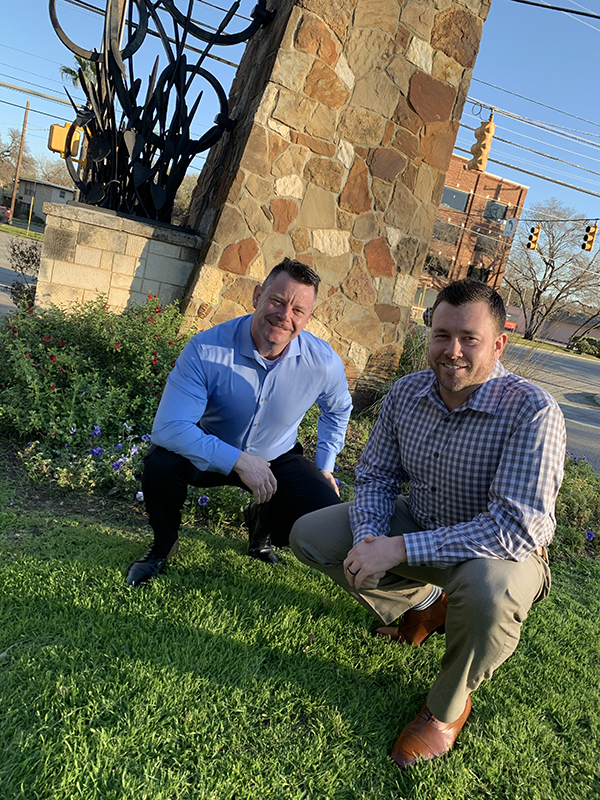 Two men kneeling in the grass near a flower bed, smiling for the camera