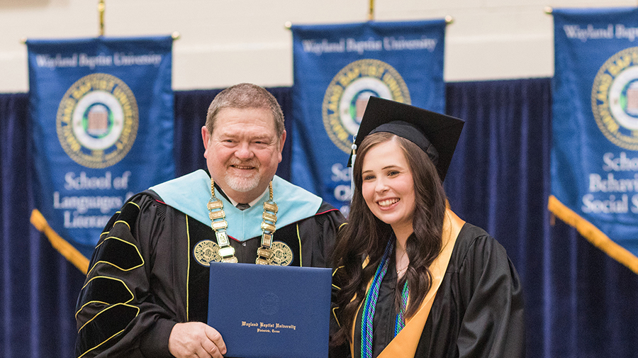 A man in doctoral academic regalia poses for a pictures as he presents a diploma to a young woman.