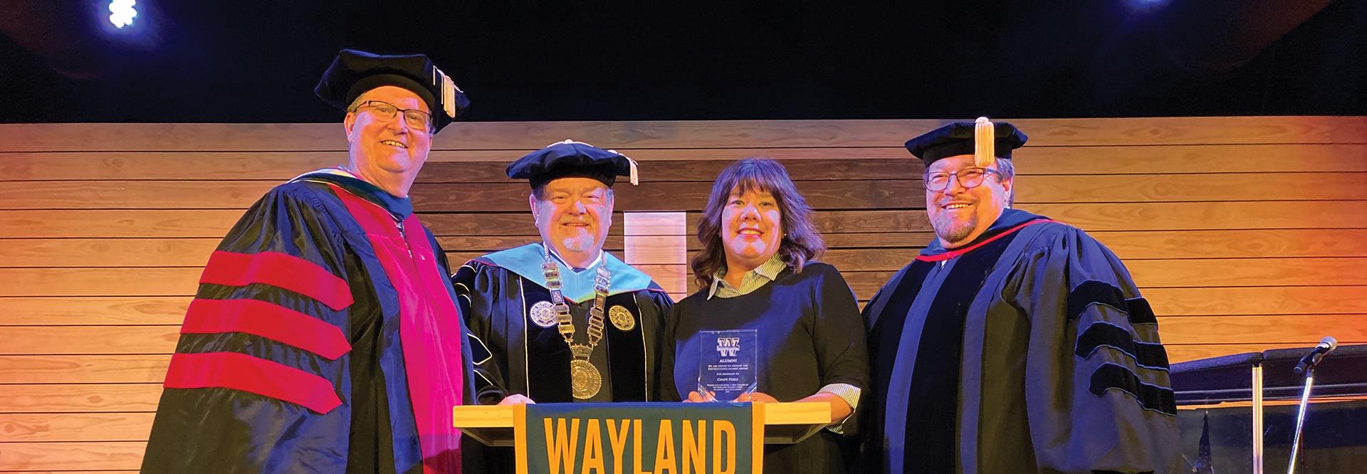 Three men in academic regalia present a woman with a crystal award
