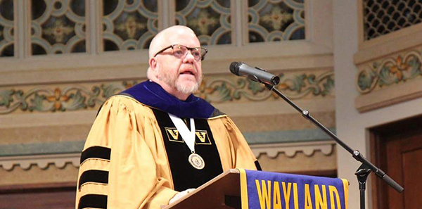 A man in yellow and black graduation regalia stands at a podium with a Wayland banner draped in front.