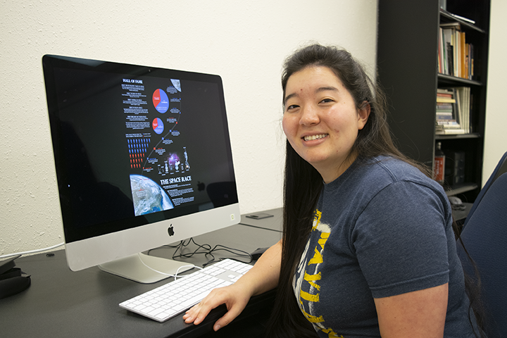 Young woman sitting in front of a computer monitor
