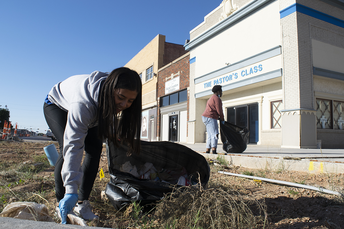 A young woman, Audrie Blanco, picks up trash near a curb