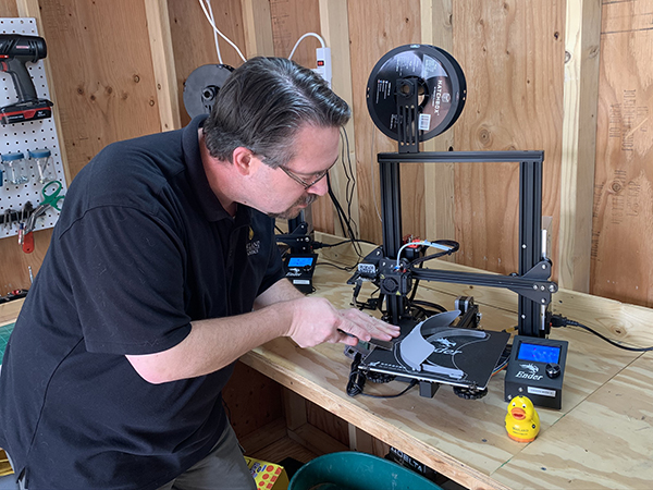 Man works with 3D printer