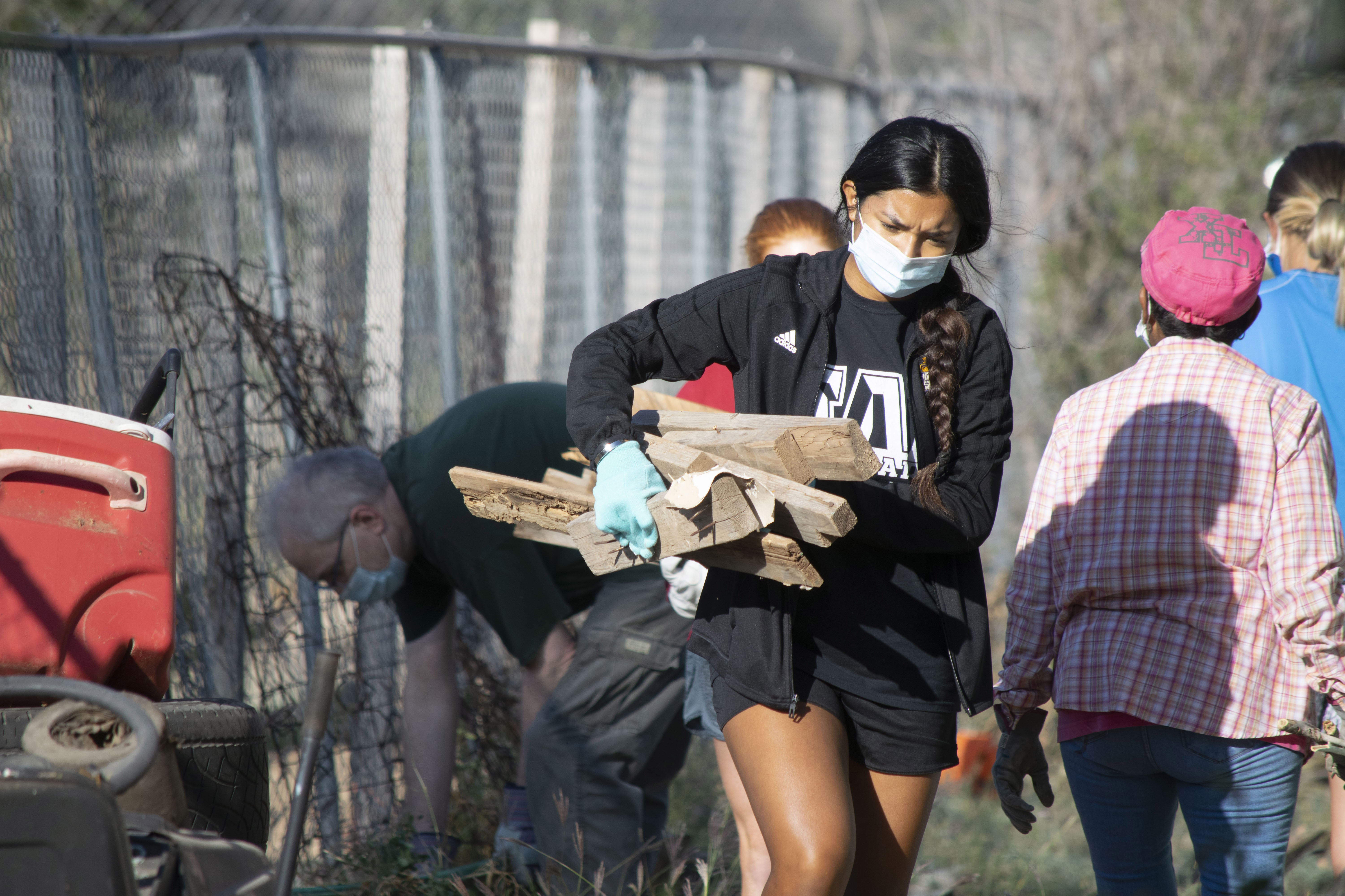 Young woman in a facemask carries an armful of debris to a trash pile while other work in the background.