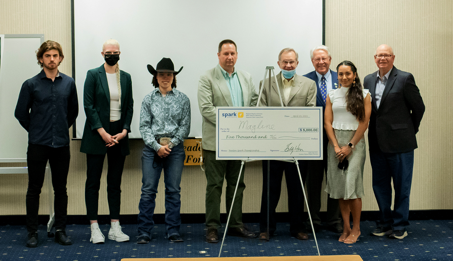 Eight individuals line a stage, standing behind an easel that is holding a fake $5,000 check.