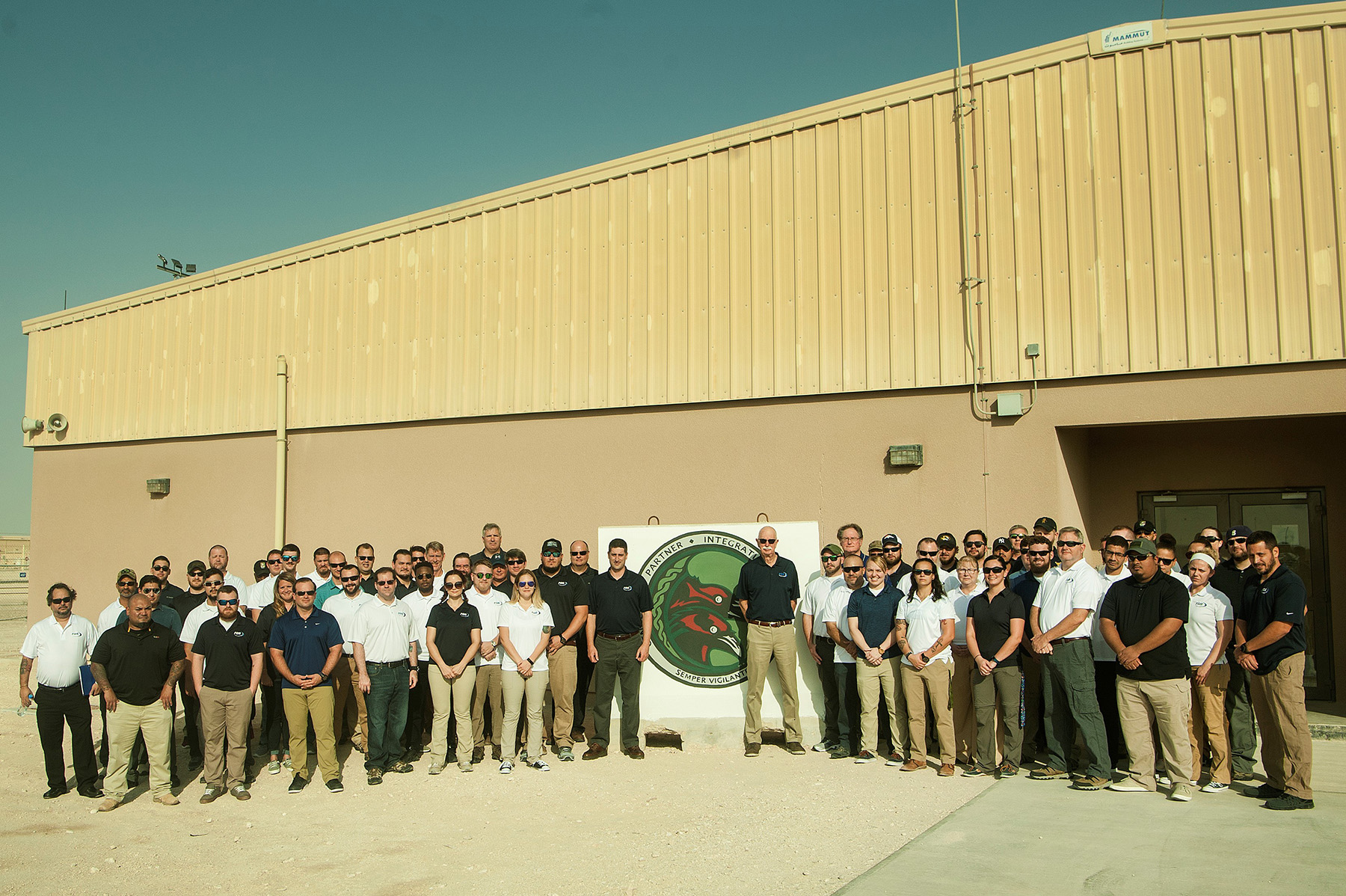 Johnson (center) with FGS employees in Qatar