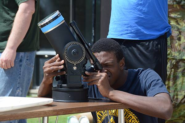 A Wayland student uses a telescope to view the solar eclipse.