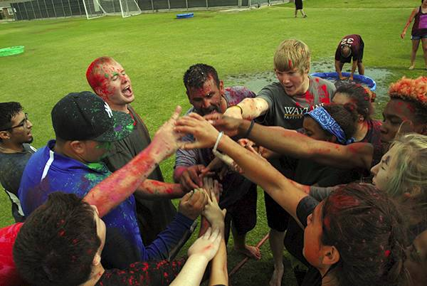 Students huddle together during a Messy Games event at Koinonia.