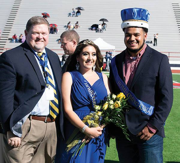 Homecoming Queen and King standing with another man on the football field.