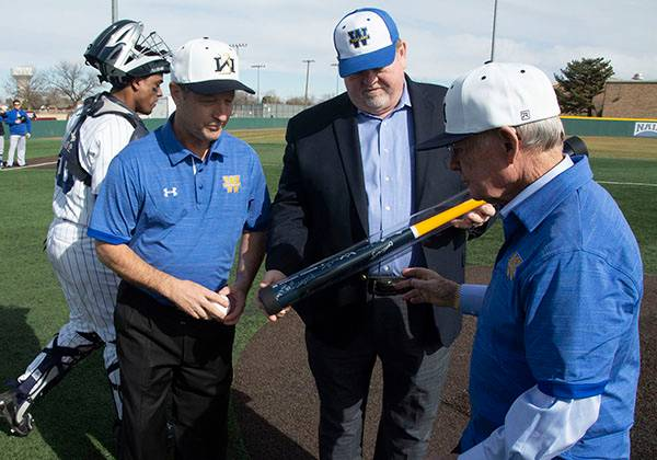 A man shows an autographed bat to two other men