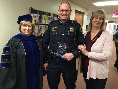 Clovis Police Chief Doug Ford (center) holds the award for Distinguished Alumni of the Clovis Campus, joined by Wayland VP for External Programs Dr. Elane Seebo (left) and Ford's wife Jane.