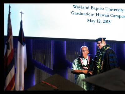 Howard DeMotta, left, receives the Distinguished Alumni Award from Hawaii campus Executive Director Dr. Dan Jacobson at the May 12 graduation ceremony.