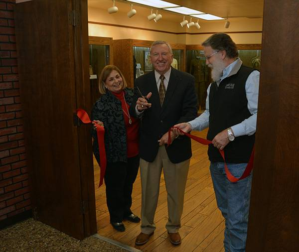 Three people cut a red ribbon to open an exhibit